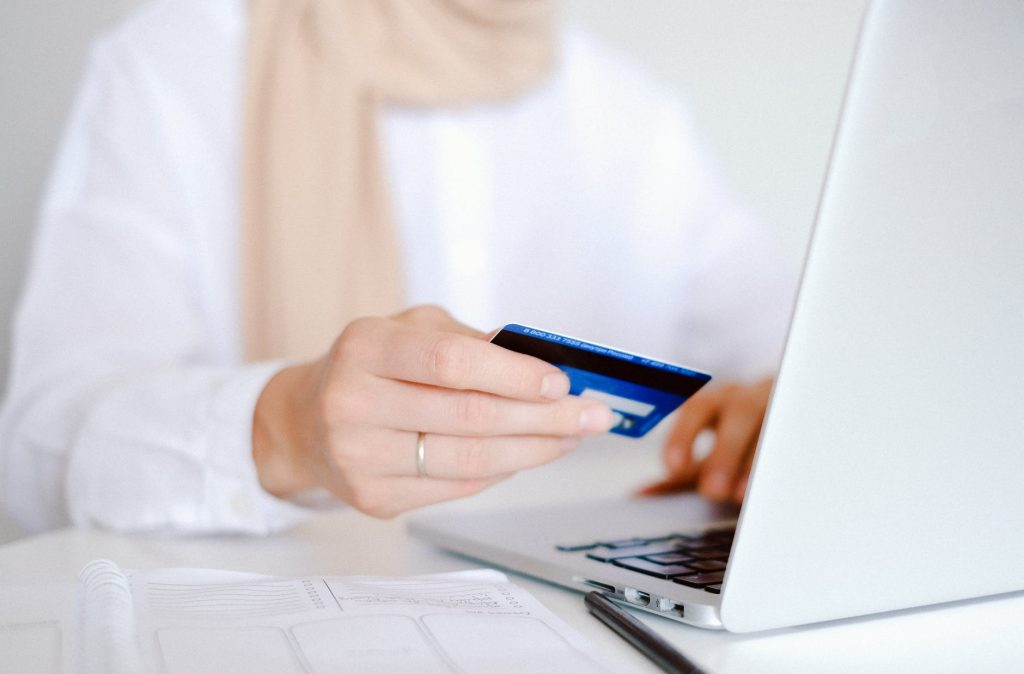 online banking/woman holding bank card in front of computer